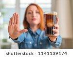 redhead woman holding soda...