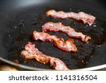 slices of fresh fried bacon in... | Shutterstock . vector #1141316504