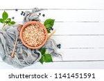 dry oatmeal porridge in a plate.... | Shutterstock . vector #1141451591