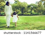 mom and little daugther walking ... | Shutterstock . vector #1141566677