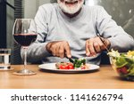 happy senior man eating pork... | Shutterstock . vector #1141626794