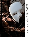 Masquerade - Phantom of the Opera Mask on Rusty Chainlink Fence - stock photo