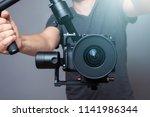 Cameraman holding gimbal with slr camera - stock photo