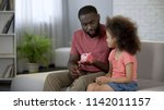 father giving piggy bank to... | Shutterstock . vector #1142011157