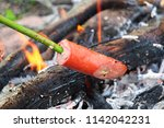 cooking sausage on a stick over ... | Shutterstock . vector #1142042231