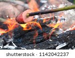 cooking sausage on a stick over ... | Shutterstock . vector #1142042237