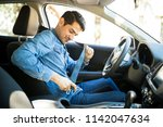 young latin man sitting on car... | Shutterstock . vector #1142047634
