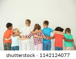 Little children hugging each other with hands on light background. Unity concept