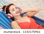 young woman listening to music... | Shutterstock . vector #1142170961