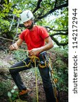 mountain rescuer securing ropes ... | Shutterstock . vector #1142172944