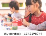 asian girl is drawing in... | Shutterstock . vector #1142198744
