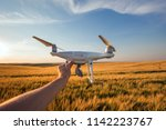 the white drone in hands at the ... | Shutterstock . vector #1142223767