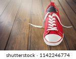 new red sneakers on wood... | Shutterstock . vector #1142246774