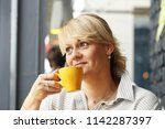 woman with yellow cup with...   Shutterstock . vector #1142287397