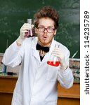 Small photo of Mad scientist shows two flasks with colored liquid in his laboratory