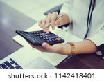 close up on senior accountant... | Shutterstock . vector #1142418401