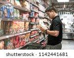 asian man choosing instant... | Shutterstock . vector #1142441681