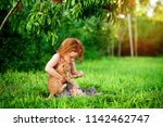 Stock photo little girl playing with pet cat outdoors in the garden countryside view happy kid is sitting on 1142462747