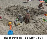 children dig a hole in the sand ... | Shutterstock . vector #1142547584