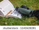 binoculars and bird guide | Shutterstock . vector #1142628281