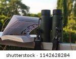binoculars and bird guide ... | Shutterstock . vector #1142628284