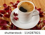 coffee cup with petals on table - stock photo