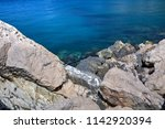 blue sea water and rocky shore... | Shutterstock . vector #1142920394