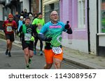 Small photo of Hastings,East Sussex/UK 03-18-18 Hastings half marathon 2018. Four runners sprint down All Saints Street in the old town and runner 2301 is filming the experience