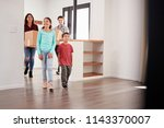 excited family carrying boxes... | Shutterstock . vector #1143370007