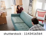 couple surrounded by boxes... | Shutterstock . vector #1143416564