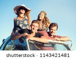 group of happy friends in a car ... | Shutterstock . vector #1143421481