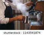 Coffee shop worker preparing coffee on steam espresso coffee machine. Cropped shot of man working in coffee shop wearing an apron. - stock photo
