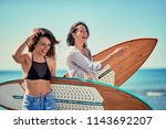 smiling women surfers walking... | Shutterstock . vector #1143692207