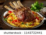 Oriental rack of lamb with saffron rice and roasted vegetables marinated and seasoned with spices and fresh herbs served on a platter