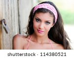 Portrait of a beautiful mixed woman with pink hair scarf - stock photo