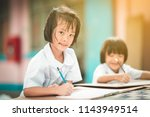 asian happy kid student writing ... | Shutterstock . vector #1143949514