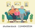 happy grandparents reading book ... | Shutterstock .eps vector #1144043534