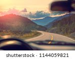 driving a car on mountain road. ... | Shutterstock . vector #1144059821