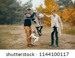 Stock photo happy parents have fun and lift up their daughter at forest path next to jumping dog during walk in 1144100117