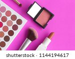Small photo of Cosmetic set, eye shadow palette, lipstick, brushes, and blush, placed on a hot pink background with a selective focus