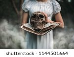 female victim holds book and... | Shutterstock . vector #1144501664