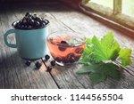 mug of black currants  glass... | Shutterstock . vector #1144565504