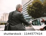 mature businessman getting into ... | Shutterstock . vector #1144577414
