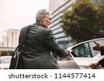mature businessman getting into ... | Shutterstock . vector #1144577414