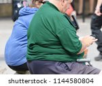 Small photo of Somerset, UK. July 28 2018. A morbidly obese couple sit on a bench in the street. Almost 1 in 3 British adults are now estimated to be obese with the majority of the population being overweight.