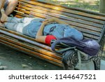 the girl is sleeping on a park... | Shutterstock . vector #1144647521