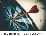 Stock photo close up shot of the dart arrow hit on bulleyes of dartboard to represent that the business reached 1144665047
