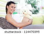 Smiling pregnant woman lying on couch with teddy bear - stock photo