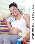 cheerful pregnant woman shoving bought things for your baby - stock photo