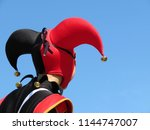 Small photo of Person in a jester costume isolated on clear blue sky, carnival concept. Actor in black-red foolscap with bells. Joker head close-up, back view